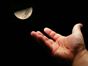 Human hand reaching towards half moon in the night sky