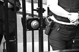 Closeup of a locked gate with a security guard