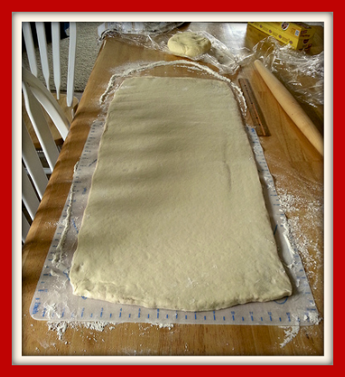 Pastry dough rolled out on floured wooden table