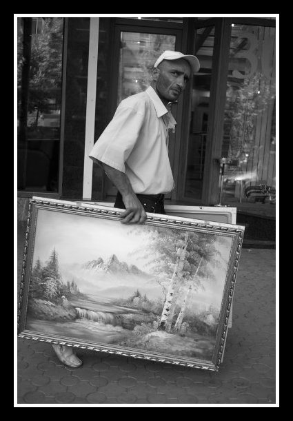 Suspicious guy holding two framed paintings